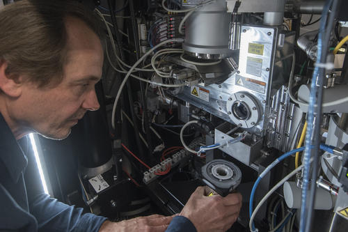 Christoph Böttcher, scientific head of the Research Center of Electron Microscopy at the Institute of Chemistry and Biochemistry, introduces a container with the snap-frozen preparation into the high-vacuum chamber of an electron microscope.