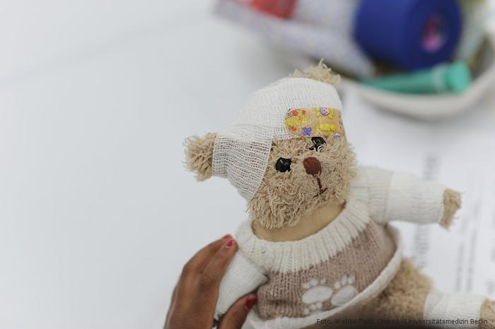 "In der Teddyklinik können In the Teddy Bear Clinic, children can take their stuffed animals to be ""treated"" by medical students."